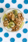 Exponeringsglas med vanlig yoghurt med kiwin och muttrar Royaltyfri Fotografi
