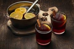 Exponeringsglas med varmt funderat vin och en bunke för förberedelsen av en dryck arkivfoto