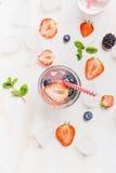 Exponeringsglas med vatten, bär, iskuber, rött sugrör och ingredienser på vit träbakgrund Arkivfoto