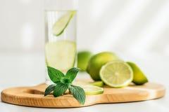 Exponeringsglas med vatten-, limefrukt- och mintkaramellsidor royaltyfria bilder