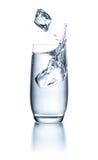 Exponeringsglas med vatten med iskuber och färgstänk Arkivbilder