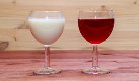 Exponeringsglas med vin och mjölkar Arkivfoton