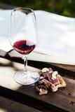 Exponeringsglas med vin och stycken av för choklad den öppna boken nära Royaltyfri Fotografi