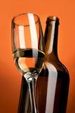 Exponeringsglas med vitt vin och flaskan på lutningbakgrund Royaltyfria Bilder