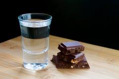 Exponeringsglas med vodka och choklad på trätabellen och svart bakgrund royaltyfria foton
