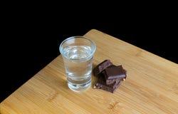 Exponeringsglas med vodka och choklad på trätabellen och svart bakgrund fotografering för bildbyråer