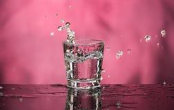 Exponeringsglas med vodka och en stor färgstänk på en kulör bakgrund arkivbild