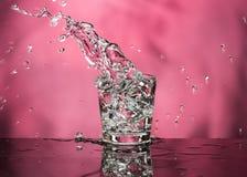 Exponeringsglas med vodka och en stor f?rgst?nk p? en kul?r bakgrund royaltyfria foton