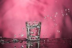 Exponeringsglas med vodka och en stor f?rgst?nk p? en kul?r bakgrund arkivbild