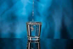 Exponeringsglas med vodka och en stor f?rgst?nk p? en kul?r bakgrund arkivfoto
