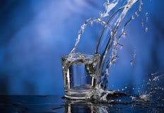 Exponeringsglas med vodka och en stor f?rgst?nk p? en kul?r bakgrund royaltyfria bilder