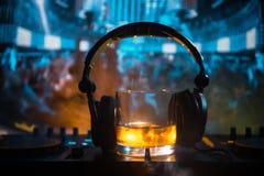 Exponeringsglas med whisky med iskuben inom på dj-kontrollant på nattklubben Dj-konsol med klubbadrinken på musikpartiet i nattkl Arkivbild