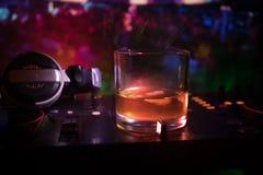 Exponeringsglas med whisky med iskuben inom på dj-kontrollant på nattklubben Dj-konsol med klubbadrinken på musikpartiet i nattkl Royaltyfri Fotografi