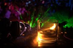 Exponeringsglas med whisky med iskuben inom på dj-kontrollant på nattklubben Dj-konsol med klubbadrinken på musikpartiet i nattkl Fotografering för Bildbyråer