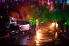 Exponeringsglas med whisky med iskuben inom på dj-kontrollant på nattklubben Dj-konsol med klubbadrinken på musikpartiet i nattkl Royaltyfri Bild