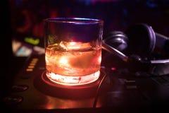 Exponeringsglas med whisky med iskuben inom på dj-kontrollant på nattklubben Dj-konsol med klubbadrinken på musikpartiet i nattkl Royaltyfria Foton