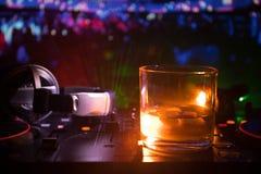 Exponeringsglas med whisky med iskuben inom på dj-kontrollant på nattklubben Dj-konsol med klubbadrinken på musikpartiet i nattkl Arkivfoton