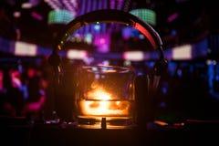 Exponeringsglas med whisky med iskuben inom på dj-kontrollant på nattklubben Dj-konsol med klubbadrinken på musikpartiet i nattkl Arkivbilder