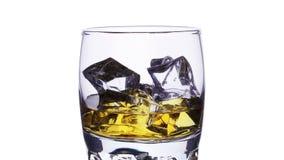 Exponeringsglas med whisky- och iskuber som fyller i effekt för zoom för stopprörelse över vit arkivfilmer