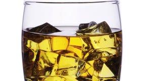 Exponeringsglas med whisky- och iskuber som tömmer i effekt för zoom för stopprörelse över vit arkivfilmer