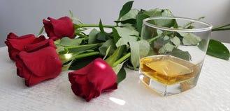 Exponeringsglas med whisky som står på den vita tabellen royaltyfri foto