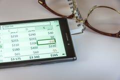 Exponeringsglas, Notepad och smart telefon Arkivfoto