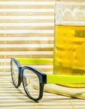 Exponeringsglas och öl i exponeringsglas på bambubakgrund Arkivbilder