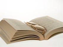 Exponeringsglas och bok Arkivfoto