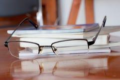 Exponeringsglas och bok på den röda wood tabellen Arkivbild