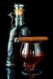Exponeringsglas och buteljerar med cognacen Royaltyfri Foto