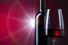 Exponeringsglas och flaska av rött vin på mörk bakgrund Arkivbilder