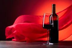 Exponeringsglas och flaska av redevin på en röd bakgrund Rött rent f royaltyfri bild