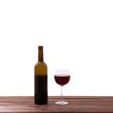 Exponeringsglas och flaska av rött vin på den isolerade trätabellen Arkivfoton