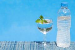 Exponeringsglas och flaska av vatten på mattt bambusugrör Royaltyfri Bild