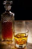 Exponeringsglas och flaska av whisky Arkivfoto