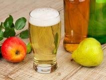 Exponeringsglas och flaskor av äppeljuice Arkivfoto