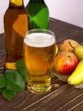Exponeringsglas och flaskor av äppeljuice Arkivfoton