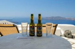 Exponeringsglas och flaskor av vulkanöl och en räkning på tabellen med det blåa havet på en bakgrund Arkivfoto