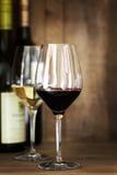 Exponeringsglas och flaskor för rött och vitt vin över ek Arkivfoto