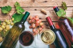 Exponeringsglas och flaskor för rött och vitt vin på träbakgrund, kopieringsutrymme Nya druvor och druvasidor som garnering Royaltyfria Bilder