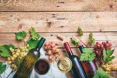 Exponeringsglas och flaskor för rött och vitt vin på träbakgrund, kopieringsutrymme Nya druvor och druvasidor som garnering Arkivbild