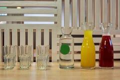 Exponeringsglas och flaskor med fruktsaft Royaltyfri Fotografi