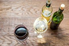 Exponeringsglas och flaskor med rött och vitt vin arkivbilder