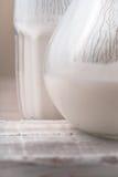 Exponeringsglas och kanna av kefir på träställningen Royaltyfri Bild