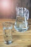 Exponeringsglas och karaff av det mest rena vattnet på trätabellen Arkivbild