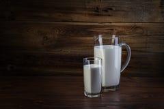 Exponeringsglas och karaffen av mjölkar Arkivfoton