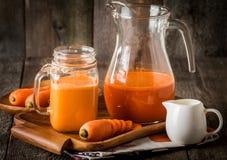 Exponeringsglas och krus av morotfruktsaft Royaltyfri Foto