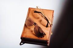 Exponeringsglas och läderanteckningsbok på en ljus bakgrund royaltyfri bild