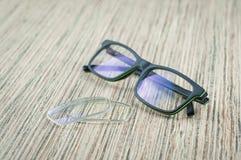 Exponeringsglas och linser för glasögon, closeup på trätabellen arkivbild