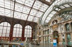 Exponeringsglas- och metallkonstruktion av järnvägsstationen Antwerpen Centraal som konstrueras i 1905 och väntande passagerare Arkivbilder
